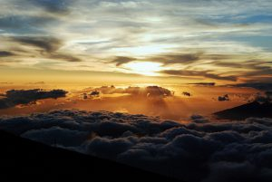 The Haleakalā sunrise over a rippling ocean of clouds.
