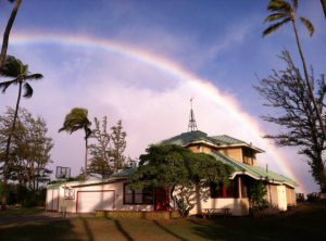 Paia Youth & Cultural Center under a rainbow sky.